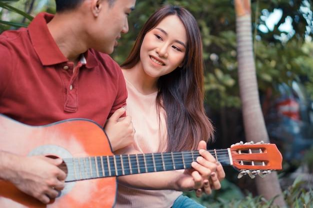 Szczęśliwa młoda para zakochanych siedzi w ogrodzie i gra na gitarze i śpiewa.