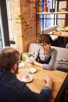 Szczęśliwa młoda para zakochanych siedzi w przytulnej kawiarni lub restauracji, przy herbacie i omawiając swoje plany