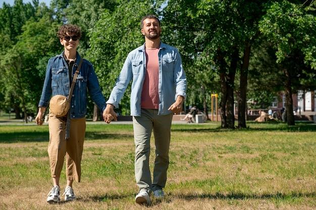 Szczęśliwa młoda para zakochanych w casual, przesuwając zielony trawnik w parku publicznym