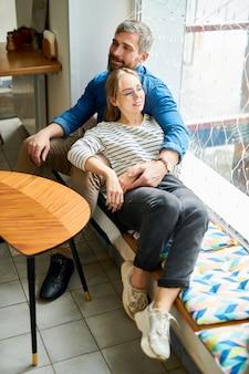 Szczęśliwa młoda para zakochanych w casual, relaks przy oknie w przytulnej kawiarni, ciesząc się romantyczną randką