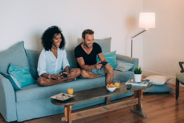 Szczęśliwa młoda para zrelaksowała się w domu na kanapie, grając w gry wideo