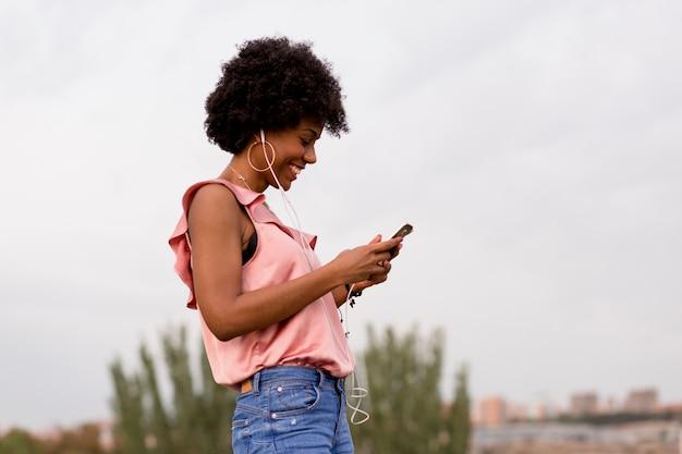 Szczęśliwa młoda piękna afro amerykańska kobieta słucha muzyka na jej telefonie komórkowym i ono uśmiecha się. tło miejskie. sezon wiosenny lub letni. codzienne ubrania.