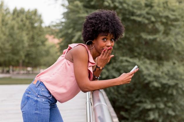 Szczęśliwa młoda piękna afro amerykańska kobieta uśmiecha się telefon komórkowego i używa. zielone tło. sezon wiosenny lub letni. codzienna odzież na zewnątrz