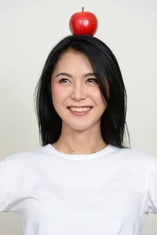 Szczęśliwa młoda piękna azjatycka kobieta myśli z jabłkiem na czubku głowy