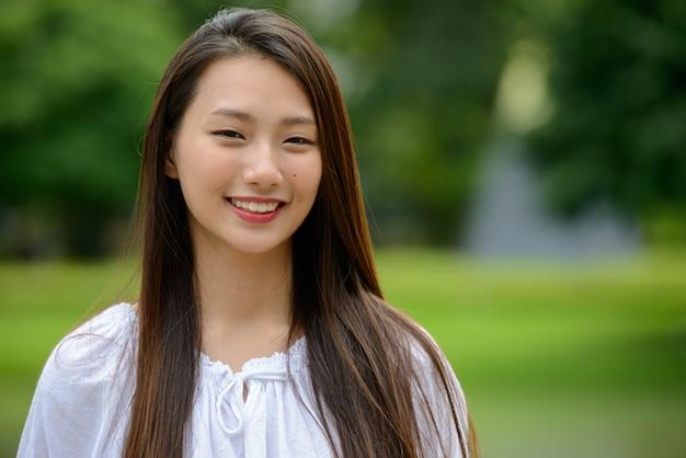 Szczęśliwa młoda piękna azjatycka nastolatka w parku