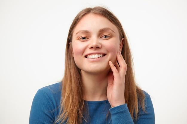 Szczęśliwa młoda piękna długowłosa kobieta z przypadkową fryzurą dotykając jej policzka z podniesioną ręką i uśmiechając się radośnie do kamery, odizolowana na białym tle