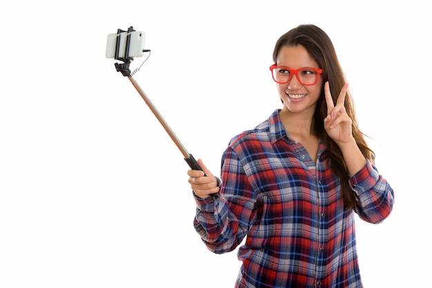 Szczęśliwa młoda piękna hipster kobieta przy selfie z telefonu na kij selfie