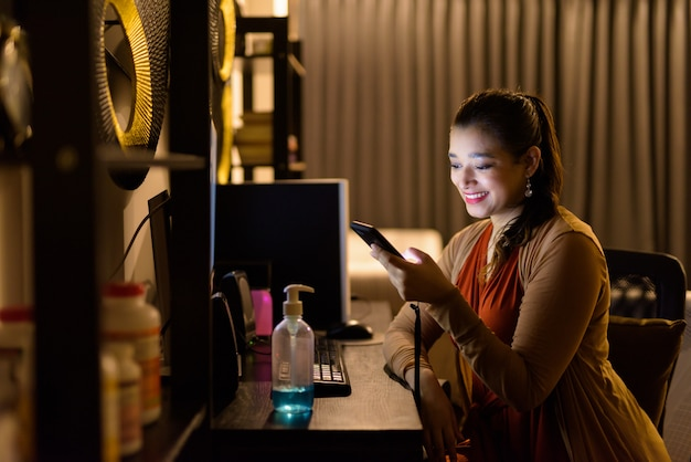 Szczęśliwa młoda piękna indiańska kobieta używa telefon i pracujący od domu póżno przy nocą