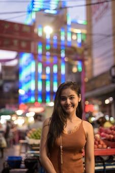 Szczęśliwa młoda piękna kobieta azjatyckich turystycznych uśmiechając się w chinatown w nocy