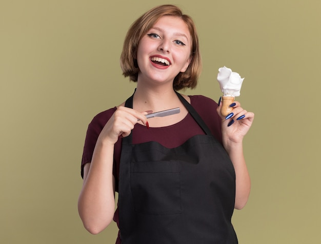 Szczęśliwa młoda piękna kobieta fryzjerka w fartuchu trzymająca brzytwę i pędzel do golenia z pianką do golenia patrząc z przodu z uśmiechem na twarzy stojącej nad zieloną ścianą