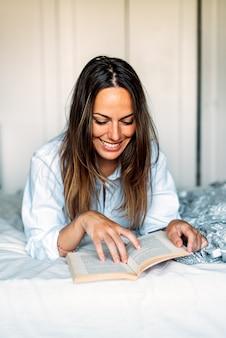 Szczęśliwa młoda piękna kobieta, leżąc na łóżku, czytając książkę