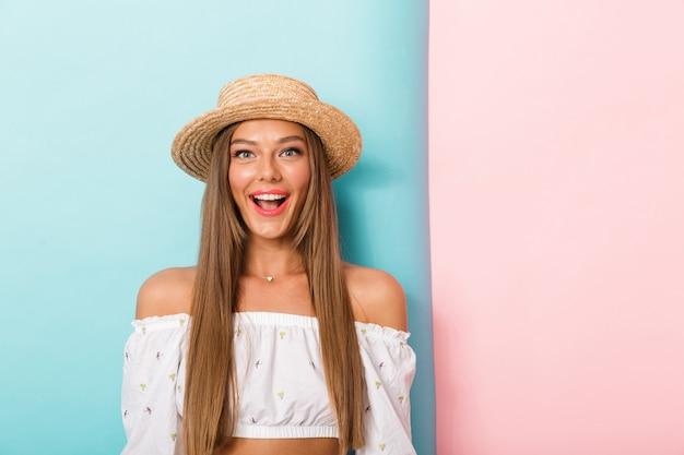 Szczęśliwa młoda piękna kobieta pozuje na białym tle na sobie kapelusz.