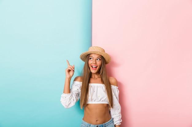 Szczęśliwa młoda piękna kobieta pozuje na białym tle sobie kapelusz pokazując copyspace.