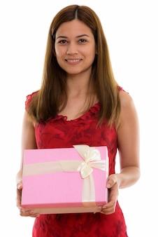 Szczęśliwa młoda piękna kobieta uśmiecha się trzymając pudełko