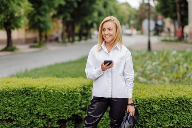 Szczęśliwa młoda piękna kobieta używa jej mądrze telefonu odprowadzenie na miasto ulicie