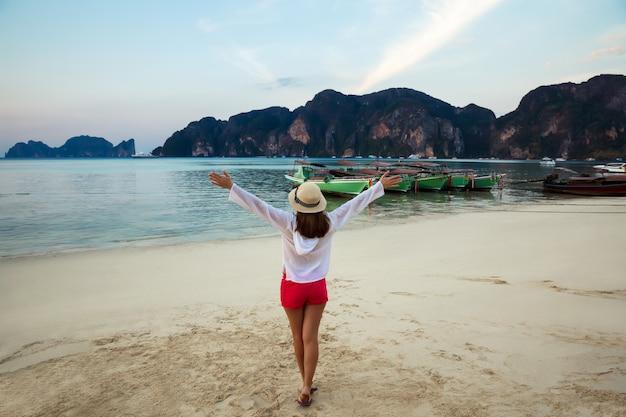 Szczęśliwa młoda piękna kobieta w kapeluszu na bezludnej tropikalnej plaży phi phi. tajlandia. koncepcja wakacje