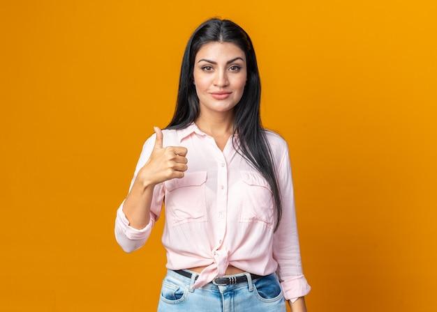 Szczęśliwa młoda piękna kobieta w zwykłych ubraniach uśmiecha się pewnie pokazując kciuk do góry stojący nad pomarańczową ścianą