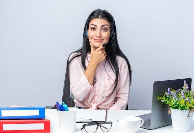 Szczęśliwa młoda piękna kobieta w zwykłych ubraniach ze słuchawkami i mikrofonem patrząc z przodu uśmiechnięty pewnie siedzący przy stole z laptopem nad białą ścianą pracujący w biurze