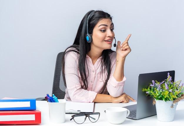 Szczęśliwa młoda piękna kobieta w zwykłych ubraniach ze słuchawkami i mikrofonem siedzi przy stole z laptopem podczas rozmowy wideo na białym tle, pracując w biurze