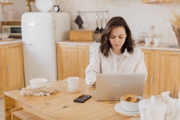 Szczęśliwa młoda piękna kobieta za pomocą laptopa w swoim nowoczesnym, jasnym mieszkaniu