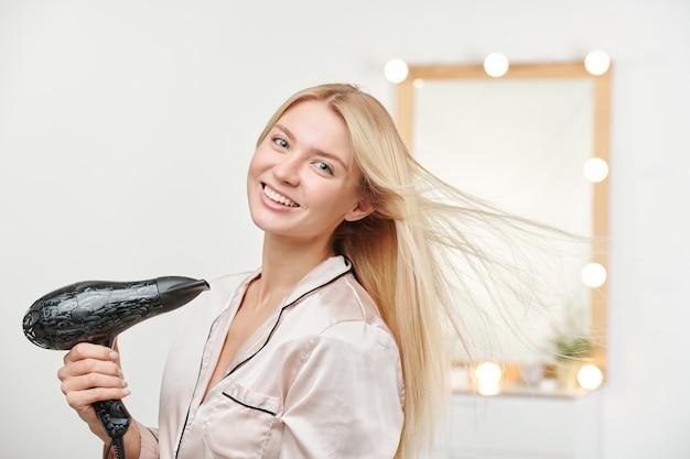 Szczęśliwa młoda piękna kobieta za pomocą suszarki do włosów po umyciu jej długie gęste zdrowe blond włosy rano