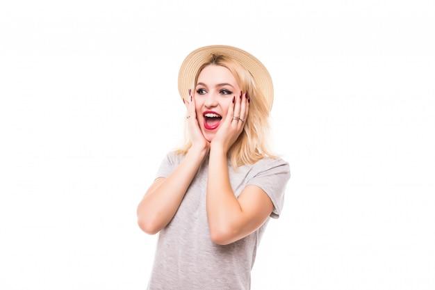 Szczęśliwa młoda piękna kobieta zdziwiona na białym tle na białej ścianie