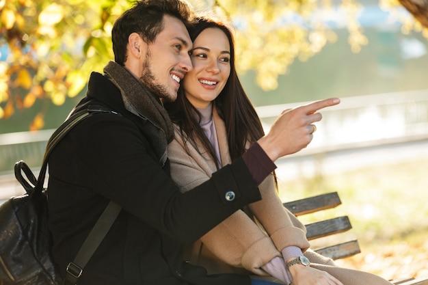 Szczęśliwa młoda piękna kochająca para pozowanie na świeżym powietrzu w parku natura siedząc na ławce wskazując.
