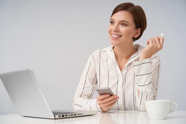 Szczęśliwa młoda piękna krótkowłosa brunetka dama z naturalnym makijażem wyjmuje słuchawki z ucha i patrzy pozytywnie przed siebie, pozując na białym