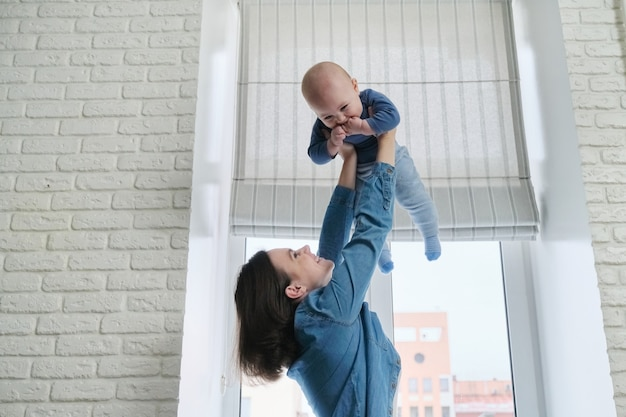 Szczęśliwa młoda piękna matka bawi się z synem malucha, kobieta wychowująca dziecko, latający i roześmiany chłopiec. rodzina jest szczęśliwa w domu, w pobliżu okna, miejsce na kopię