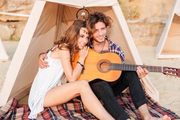 Szczęśliwa młoda piękna para siedzi z gitarą na plaży w namiocie