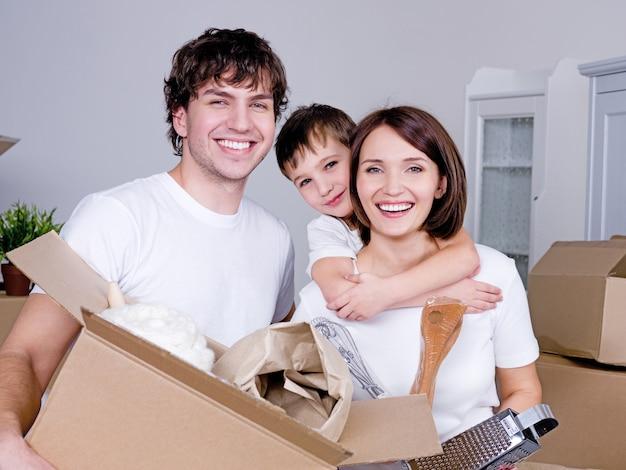 Szczęśliwa młoda przyjazna rodzina w swoim nowym mieszkaniu