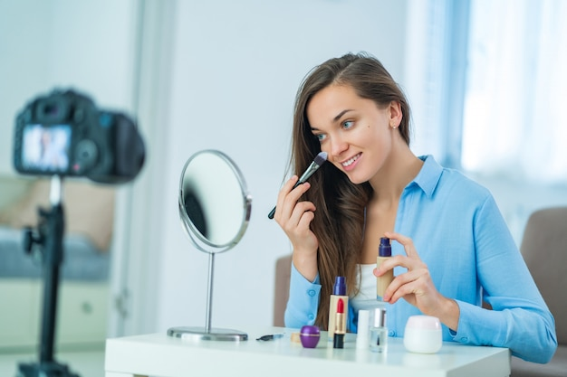 Szczęśliwa młoda radosna kobieta bloger wideo wpływowy nakładający podkład i makijaż podczas rejestrowania swojego bloga o kosmetykach w domu. blogowanie i wpływanie na odbiorców