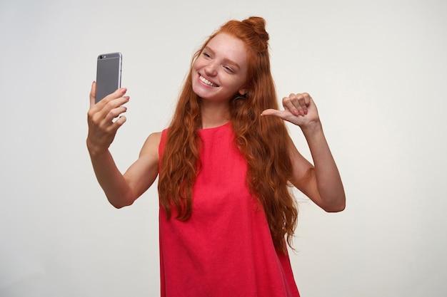 Szczęśliwa młoda readhead kobieta ubrana w włosy w węzeł, pozowanie na białym tle w swobodnej sukience, trzymając telefon komórkowy w dłoni i wskazując na siebie kciukiem podczas robienia selfie