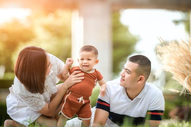 Szczęśliwa młoda rodzina azji spędzać czas na świeżym powietrzu letnie wakacje. szczęśliwa młoda rodzina spędza czas na świeżym powietrzu w ogrodzie podczas letnich wakacji. szczęśliwa rodzina, ubezpieczenie na życie, stabilność w koncepcji życia.