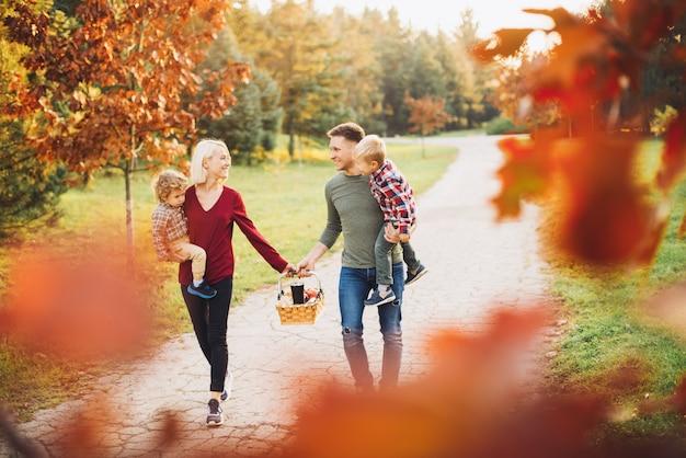 Szczęśliwa młoda rodzina chodzi w parku.