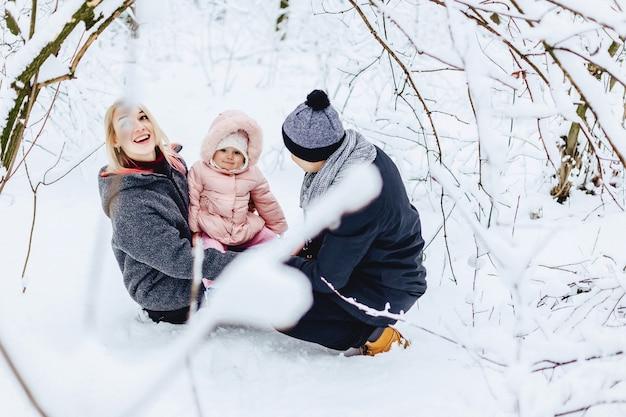 Szczęśliwa młoda rodzina chodzi z dzieckiem na zimy ulicie, mama, tata, dziecko