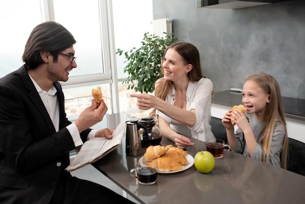Szczęśliwa młoda rodzina je śniadanie w domu