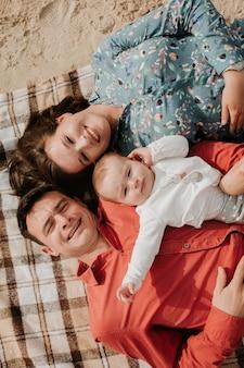 Szczęśliwa młoda rodzina leżąc na plaży