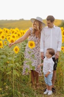 Szczęśliwa młoda rodzina, matka, ojciec i syn, uśmiechają się, trzymają i przytulają na słonecznikowym polu
