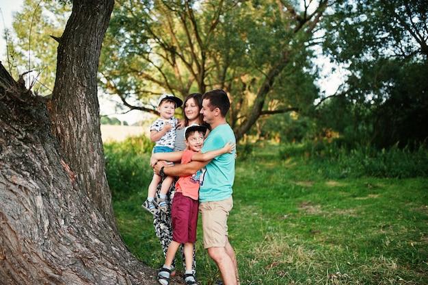 Szczęśliwa młoda rodzina: matka, ojciec, syn dwoje dzieci na charakter zabawy.