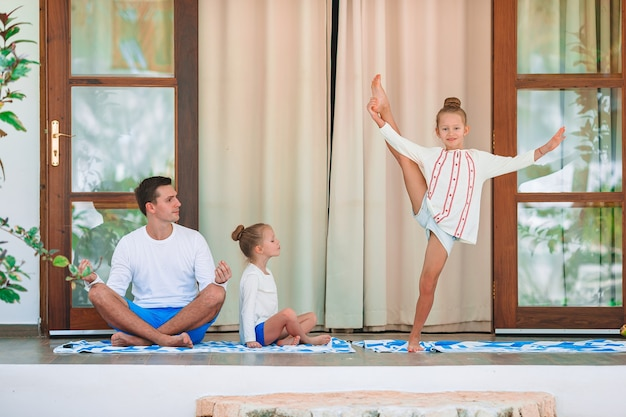 Szczęśliwa młoda rodzina medytuje na tarasie