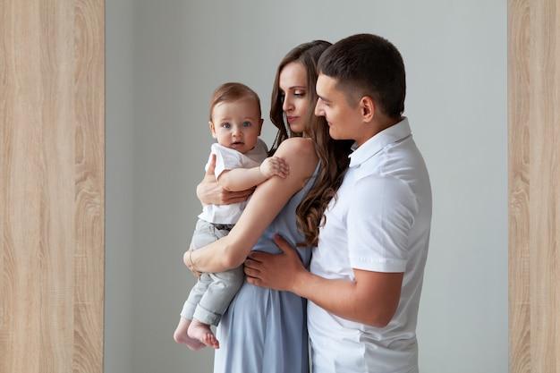 Szczęśliwa młoda rodzina na białym tle portret piękna matka i ojciec trzymający uśmiechnięte dziecko wygląda na aparat