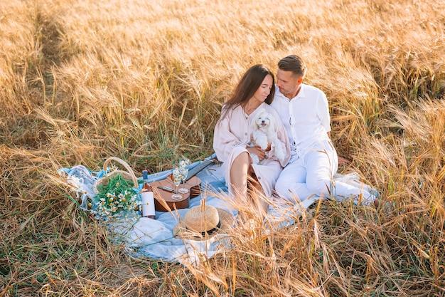 Szczęśliwa młoda rodzina na pikniku w żółtym polu pszenicy