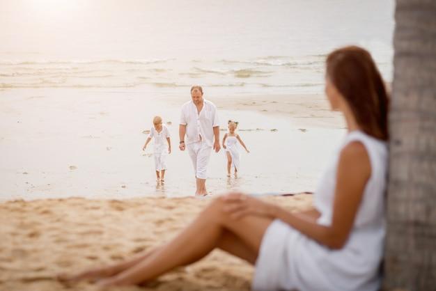 Szczęśliwa młoda rodzina na zmierzchu przy plażą.