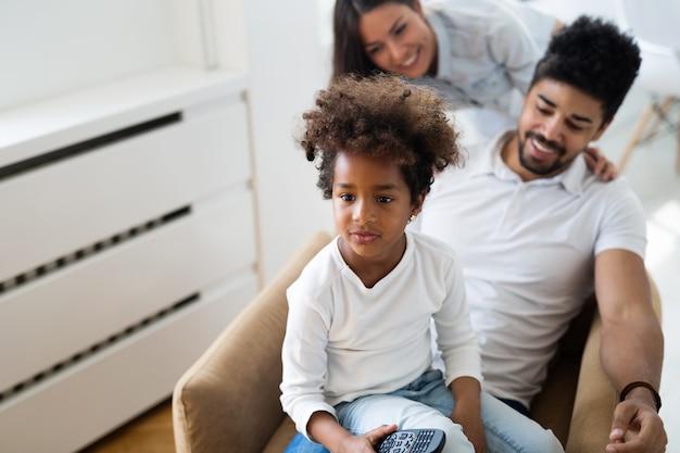 Szczęśliwa młoda rodzina odpoczywa i bawi się w nowoczesnym domu