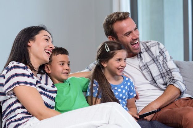 Szczęśliwa młoda rodzina ogląda telewizję z dwójką dzieci