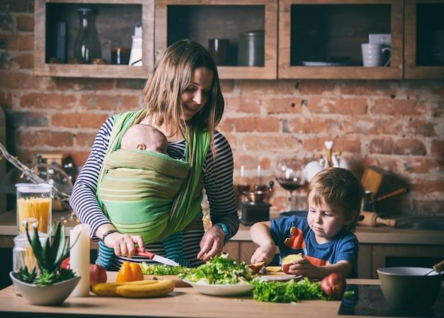 Szczęśliwa młoda rodzina, piękna matka z dwójką dzieci, uroczy chłopiec w wieku przedszkolnym i dziecko w chuście gotujące razem w słonecznej kuchni.