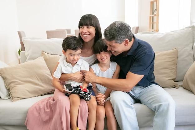 Szczęśliwa młoda rodzina razem siedzi na kanapie i uśmiecha się.