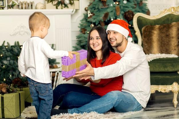 Szczęśliwa młoda rodzina razem spędza święta bożego narodzenia. wspaniałe szczęśliwe dzieciństwo.
