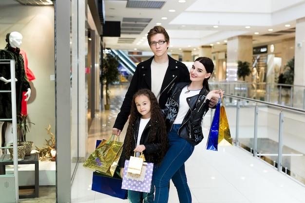Szczęśliwa młoda rodzina robi zakupy przy centrum handlowym z papierowymi torbami. kupuj okna z ubraniami